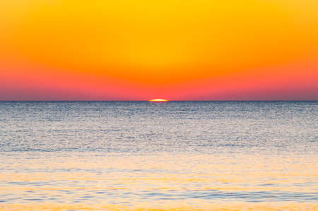 The last seconds of the amazing sundown behind the sea horizon. A bit of the sun star sphere showing up above the Tyrrhenian sea level. Vibrant sunset on Cala Violina beach, Scarlino, Grosetto, Italy Stock Photo - 133739300