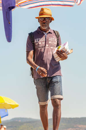 Tenda Gialla, Province of Grosseto, Tuscany, Italy - September 03, 2019: Man holding showing offering selling various printed books while walking on the beach between resting tourists