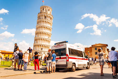 Pisa, Italy - September 03, 2019: The famous leaning Tower of Pisa or La Torre di Pisa at the Cathedral Square, Piazza del Duomo full of tourists and ambulance on duty in Pisa, Italy