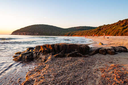 Cala Violina, Grosetto, Italy - September 03, 2019: People resting on scenic beach Cala Violina at the sunset. Tyrrhenian Sea bay at the sunset. Editorial