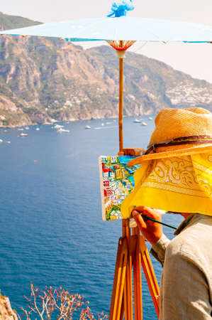 Positano, Italy - September 05, 2019: The artist painting scenery of a beautiful Positano city coast scenic rocky surroundings on one of a cliffs with blue sea waters full of yachts and high mountains