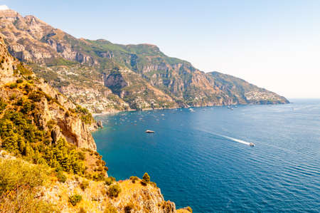 Beautiful scenic landscape of Positano, Italy. Rocky coastline full of boats and yachts traveling near high mountains. Cityscape of Positano surrounded by hills and deep blue Tyrrhenian sea waters