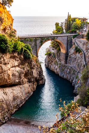 View on Fiordo di Furore arc bridge built between high rocky cliffs above the Tyrrhenian sea bay in Campania region in Italy. Unique cove under the cliffs, natural gorge, canyon or fiord