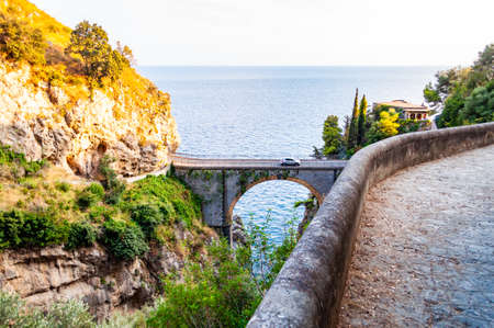 View on Fiordo di Furore arc bridge built between high rocky cliffs above the Tyrrhenian sea bay in Campania region in Italy. Curved walkway on the mountain around the unique nature gorge