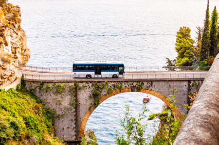View on Fiordo di Furore arc bridge built between high rocky cliffs above the Tyrrhenian sea bay in Campania region in Italy. Bus driving on the bridge, boat floating by the unique cove under