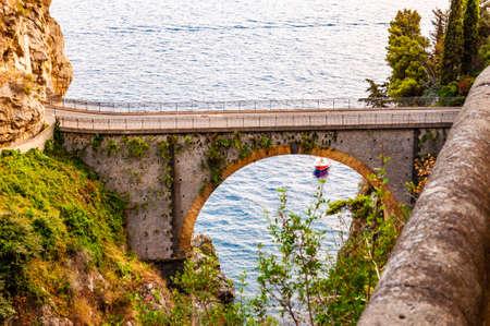 View on Fiordo di Furore arc bridge built between high rocky cliffs above the Tyrrhenian sea bay in Campania region in Italy. Boat floating by the unique cove under the bridge