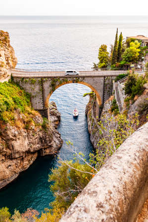 View on Fiordo di Furore arc bridge built between high rocky cliffs above the Tyrrhenian sea bay in Campania region in Italy. Car driving on the bridge, boat floating by the unique cove under