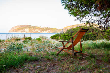 Wooden deckchair with yellow fabric back on the grass surrounded by trees and plants with Tyrrhenian sea coast and mountains on the background in Campania, Italy