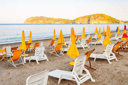 White plastic and metal construction with yellow fabric deckchairs together with yellow umbrellas on the sand beach of Tyrrhenian sea with mountains on background in Campania, Italy Reklamní fotografie