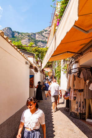 Positano, Italy - September 05, 2019: Amazing medieval Positano cityscape on rocky landscape, people and tourists walking by the cozy streets full of art galleries, shops and local businesses 新聞圖片