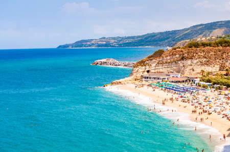 Landscape view on famous Rotonda Beach full of resting sunbathing and swimming people. Popular sea promenade in Tropea city in Italy