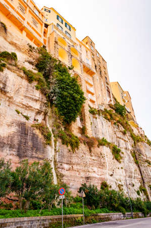 Famous sea promenade in Tropea with high cliffs with built on top city buildings and apartments. Overgrown with southern plants rocks as strong foundation for the buildings. Italian architecture.