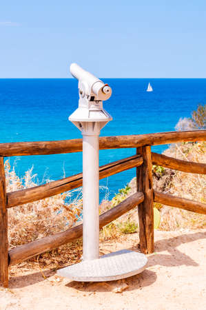 Stationary touristic telescope made of metal on one leg standing on the edge of a cliff near the wooden logs fence and observes the Tyrrhenian sea with floating white sailing yacht in Tropea, Italy