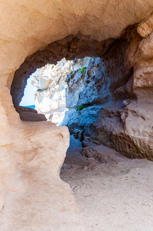 Side view on the round entrance tunnel to unique sea cave in massive rock in Tropea city near the famous Rotonda beach. Tyrrhenian sea shore in Southern Italy in Calabria. Reklamní fotografie