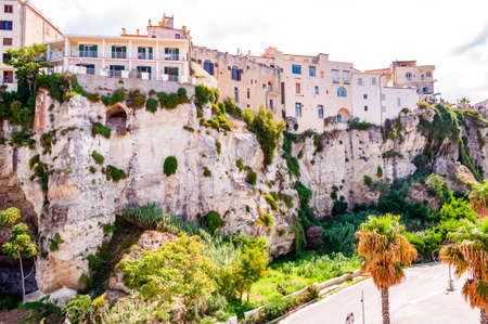 Famous sea promenade in Tropea with high cliffs with built on top city buildings and apartments. Parking area on the street. Amazing Italian cityscape