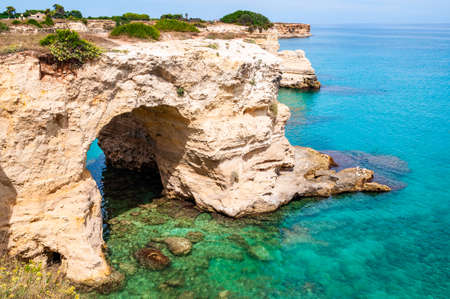 Torre Sant Andrea beach with its soft calcareous rocks and cliffs, sea stacks, small coves and the jagged coast landscape. Crystal clear water shaping white stone creating natural arcs and caves