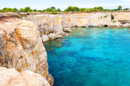 Crystal clear water on Torre Sant Andrea beach with its jagged coast landscape. Ionian sea bay in Melendugno, Puglia, Italy