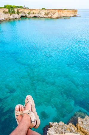 Sitting on the edge of a cliff with dangling legs in travel sandals looking on crystal clear water on Torre Sant Andrea beach with its jagged coast landscape