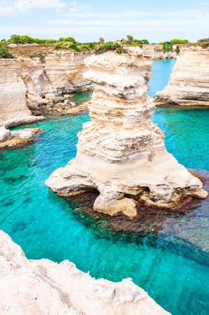 Torre Sant Andrea beach with its soft calcareous rocks and cliffs, sea stacks, small coves and the jagged coast landscape. Crystal clear water shaping white stone creating natural arcs and columns