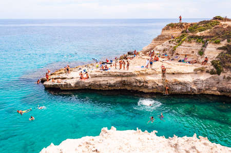 Tropea, Calabria, Italy - September 09, 2019: People diving from the flat cliff, sunbathing, swimming in crystal clear sea water on the rocky beach Torre Sant Andrea with rocks, cliffs and sea stacks