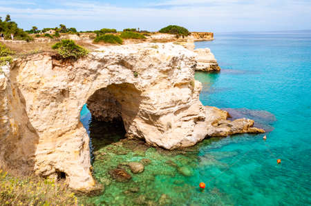 Tropea, Calabria, Italy - September 09, 2019: Torre Sant Andrea beach with its soft calcareous rocks and cliffs, sea stacks, small coves and the jagged coast landscape