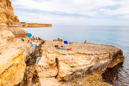 Tropea, Calabria, Italy - September 09, 2019: People diving from the cliff, sunbathing, swimming in crystal clear sea water on the rocky beach Torre Sant Andrea with rocks, cliffs and sea stacks