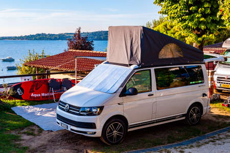Camping La Ca, Garda Lake, Lombardy, Italy - September 12, 2019: Volkswagen camper van parked near the coast of Garda lake in camping La Ca located on the southern shore of the lake Editorial