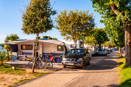 Camping La Ca, Garda Lake, Lombardy, Italy - September 12, 2019: Cozy inside landscape design of camping La Ca located on the southern shore of Garda lake. Area for tents, campers, bungalows, houses Redactioneel