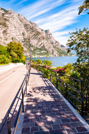 Cozy city street of Limone Sul Garda with paving stone sidewalk, blooming flowers on a metal railings, growing trees with amazing Garda lake and dolomite mountains on the background