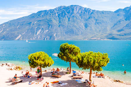 Limone Sul Garda, Lombardy, Italy - September 12, 2019: Cozy beach on western coast of the lake. People swimming sunbathing on the shore under high evergreen pines. Garda, dolomites on the background