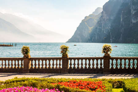 Garda lake promenade with colorful flowerbeds with growing and blooming plants, classic stone fence built on the edge with flowerpots with blooming flowers. Garda lake and high mountains on background 版權商用圖片 - 136420973
