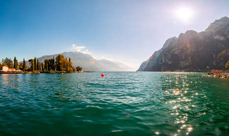 Panoramic view against bright sun rays above the rocks on beautiful Garda lake shore in Riva del Garda city in Lombardy, Italy, surrounded by high dolomite mountains 版權商用圖片 - 136420970
