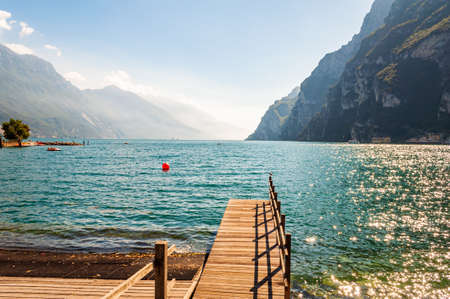 Scenic view on wooden planks pier with railings built on northern shore of beautiful Garda lake in Lombardy, Italy surrounded by high dolomite mountains and crystal clear blue water of the lake. 版權商用圖片
