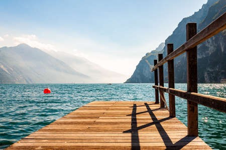Scenic view on wooden planks pier with railings built on northern shore of beautiful Garda lake in Lombardy, Italy surrounded by high dolomite mountains and crystal clear blue water of the lake. 版權商用圖片 - 136420980