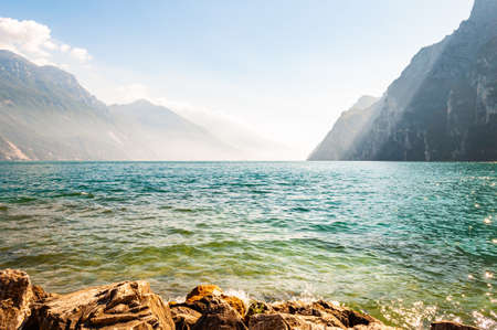Rocky stones lying on the shore of beautiful Garda lake in Lombardy, Italy surrounded by high dolomite mountains. Sun rays penetrating from above the rocks and warming misty fog above the water 版權商用圖片 - 136628743