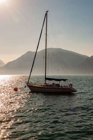 Sailing yacht floating near shore of misty Garda lake with high dolomite mountains with sun shining above in the sky on the background