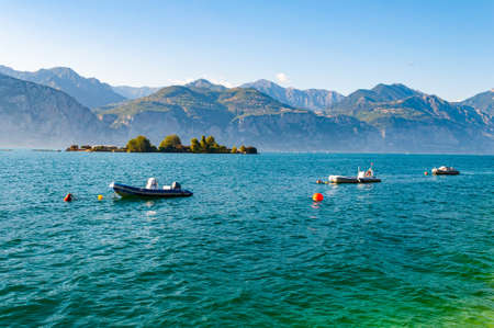 Motor boats on water, locked to parking lots floating near the shore of Garda lake with small island overgrown with trees from behind and high dolomite mountains on the background