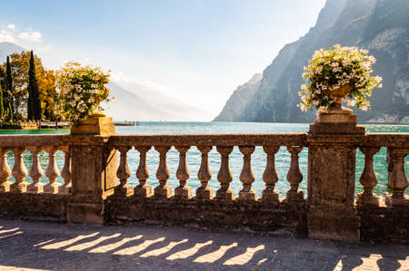 Beautiful Garda lake promenade with classic stone fence railings built on the edge with flowerpots with blooming white flowers. Garda lake surrounded by high dolomite mountains on the background