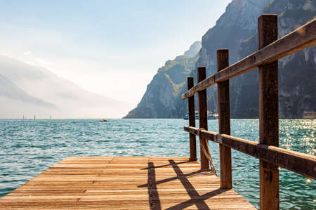 Scenic view on wooden planks pier with railings built on northern shore of beautiful Garda lake in Lombardy, Italy surrounded by high dolomite mountains and crystal clear blue water of the lake. 版權商用圖片 - 136420982