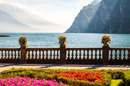 Garda lake promenade with colorful flowerbeds with growing and blooming plants, classic stone fence built on the edge with flowerpots with blooming flowers. Garda lake and high mountains on background 版權商用圖片