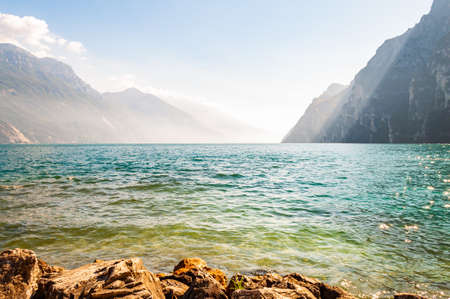 Rocky stones lying on the shore of beautiful Garda lake in Lombardy, Italy surrounded by high dolomite mountains. Sun rays penetrating from above the rocks and warming misty fog above the water 版權商用圖片