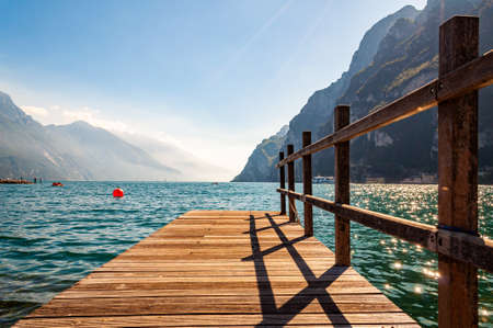 Scenic view on wooden planks pier with railings built on northern shore of beautiful Garda lake in Lombardy, Italy surrounded by high dolomite mountains and crystal clear blue water of the lake. 版權商用圖片 - 136535107