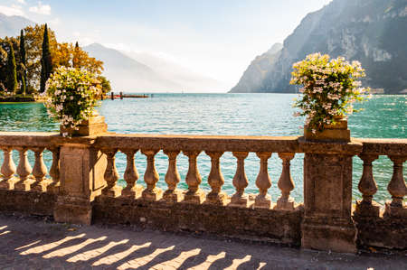 Beautiful Garda lake promenade with classic stone fence railings built on the edge with flowerpots with blooming white flowers. Garda lake surrounded by high dolomite mountains on the background 版權商用圖片 - 136420985