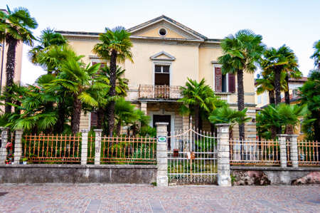 Abandoned two floors classical Italian house with growing palm in the garden metal fence and gate at the entrance in Riva del Garda, Lombardy, Italy