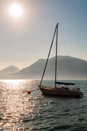 Sailing yacht floating near shore of misty Garda lake with high dolomite mountains with sun shining above in the sky on the background 版權商用圖片 - 136420981