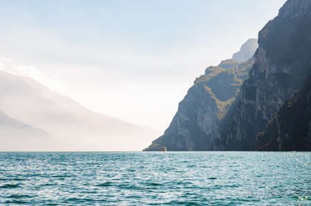 Scenic view against bright sun rays above the rocks on passenger motor ship floating on beautiful Garda lake in Lombardy, Italy surrounded by high dolomite mountains and crystal clear blue water