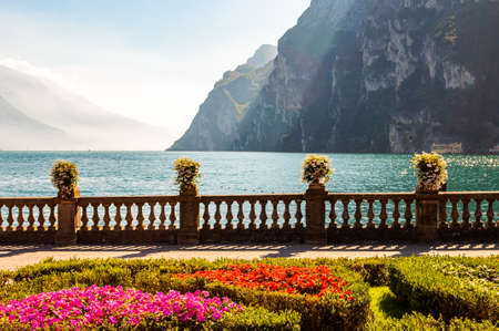 Garda lake promenade with colorful flowerbeds with growing and blooming plants, classic stone fence built on the edge with flowerpots with blooming flowers. Garda lake and high mountains on background 版權商用圖片 - 136420971