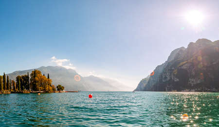 Panoramic view against bright sun rays above the rocks on beautiful Garda lake shore in Riva del Garda city in Lombardy, Italy, surrounded by high dolomite mountains
