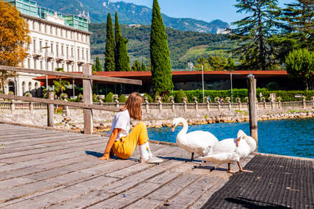 Riva del Garda, Lombardy, Italy - September 12, 2019: Tourist girl sitting on a wooden pier with two white swans walking around on promenade of Garda lake in Riva del Garda, Lombardy, Northern Italy