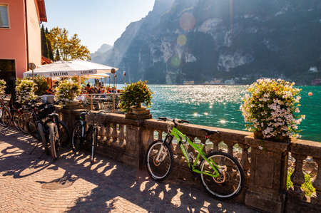 Riva del Garda, Lombardy, Italy - September 12, 2019: Bicycles parked near the stone fence railings near the outdoor restaurant full of people on Garda lake promenade with high mountains on background